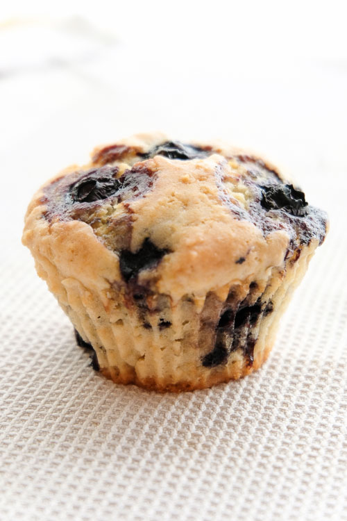 A single blueberry muffin on a white linen.