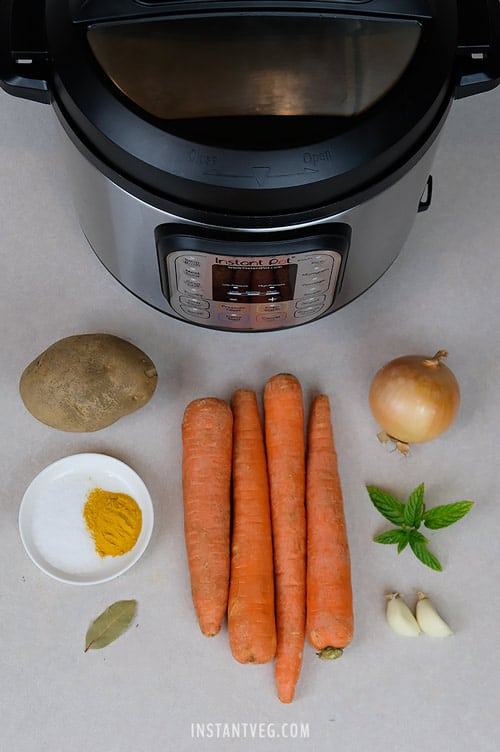 Ingredients used to make Instant Pot Vegan Carrot Soup - Carrots, Potato, Onion, Garlic, Salt, Turmeric, Bay Leaf, and Mint.