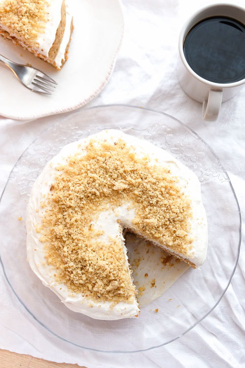 Top down view of a whole carrot cake with one slice removed, a slice of carrot cake on a plate, and cup of coffee on a table with a white tablecloth.