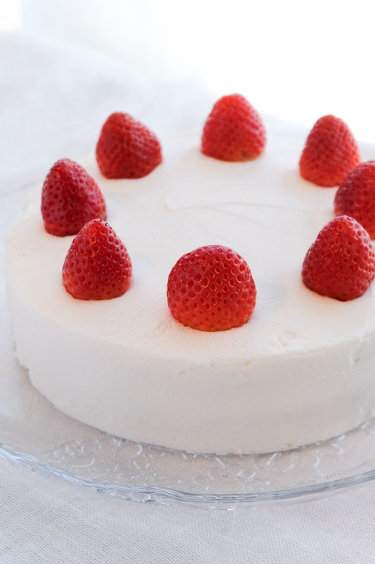 Vegan vanilla cake with white frosting and strawberries. This vegan vanilla cake is pure perfection. It's light, fluffy, and moist - with just the right amount of vanilla flavor. Top it off with my vegan buttercream frosting for a cake that's straight from heaven. #vegancake #veganvanillacake #veganwhitecake #vegancakewithstrawberries #veganbirthdaycake #bestvegancake #vegancakerecipe #veganfrosting #vegandesserts