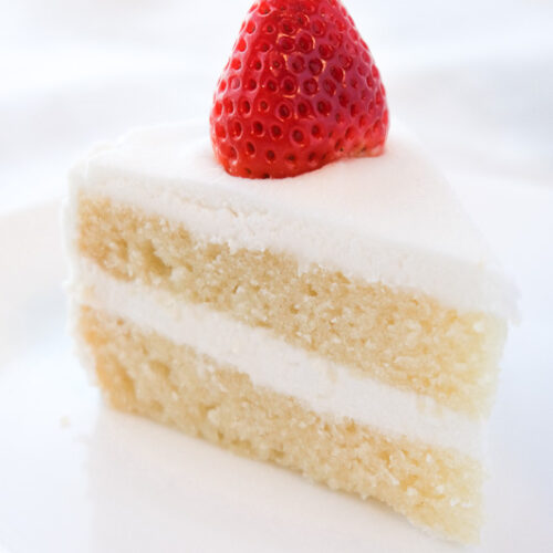 A white vegan vanilla cake slice with white frosting and strawberry.