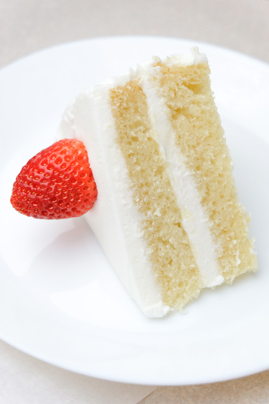 vegan white cake - vegan vanilla cake made from a fluffy spongecake with white frosting and a strawberry. This vegan vanilla cake is pure perfection. It's light, fluffy, and moist - with just the right amount of vanilla flavor. Top it off with my vegan buttercream frosting for a cake that's straight from heaven. #vegancake #veganvanillacake #veganwhitecake #vegancakewithstrawberries #veganbirthdaycake #bestvegancake #vegancakerecipe #veganfrosting #vegandesserts