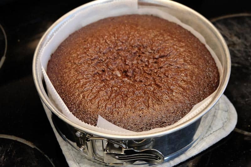 A cooked chocolate cake cooling on the stove, still in the springform pan lined with parchment paper.