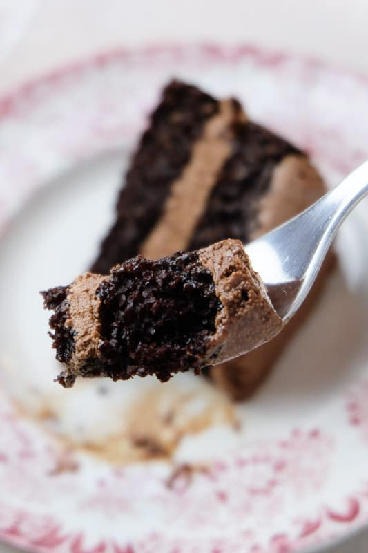 Close up shot of a bite of chocolate cake on a fork, with the rest of the slice of cake on a plate in the background.