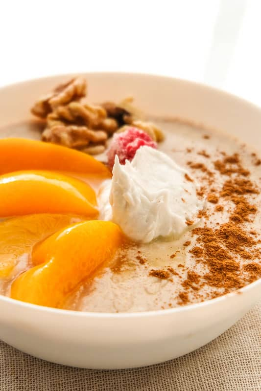 peach and raspberry smoothie bowl with coconut cream, cinnamon, walnuts, and ground flax.