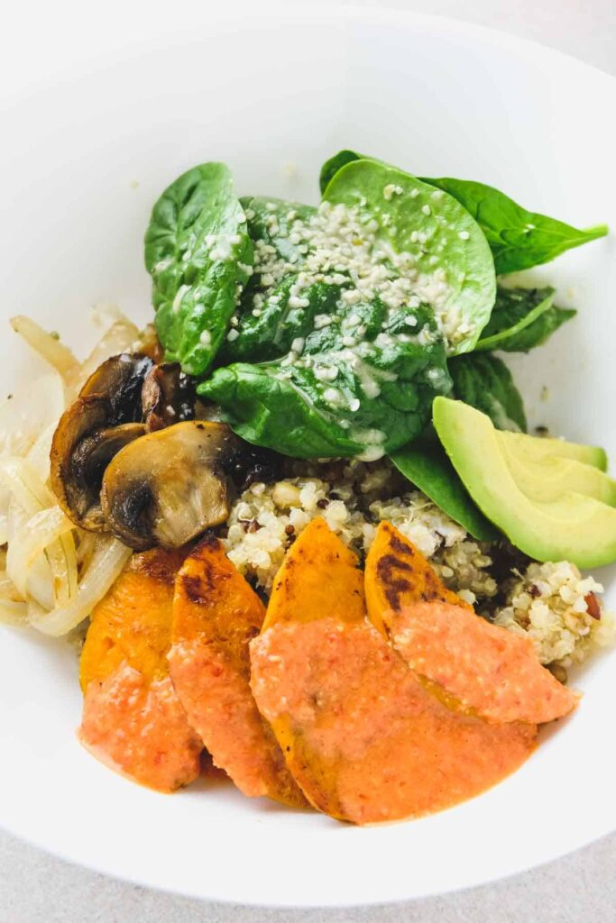 Mother Earth Bowl containing sweet potato, ancient grains, mushroom, onions, avocado, spinach, dressings, and hemp seeds.