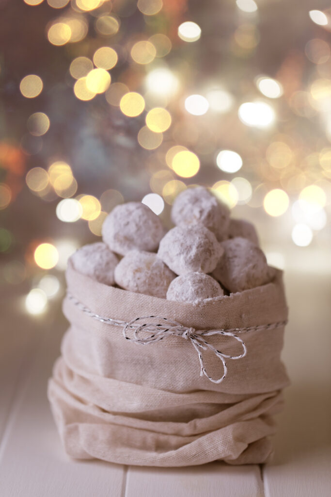 Vegan snowball cookies in a cute sack with Christmas lights in the background.