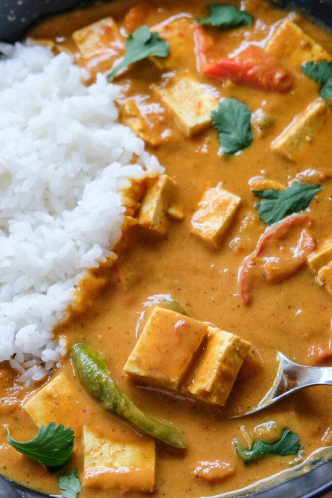 close up image of vegan instant pot curry - pieces of tofu on a spoon with butter chicken sauce and some rice.