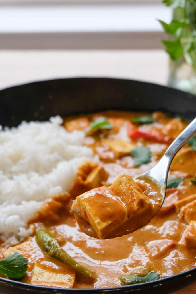 The finished vegan butter chicken with rice, being scooped up on a spoon.