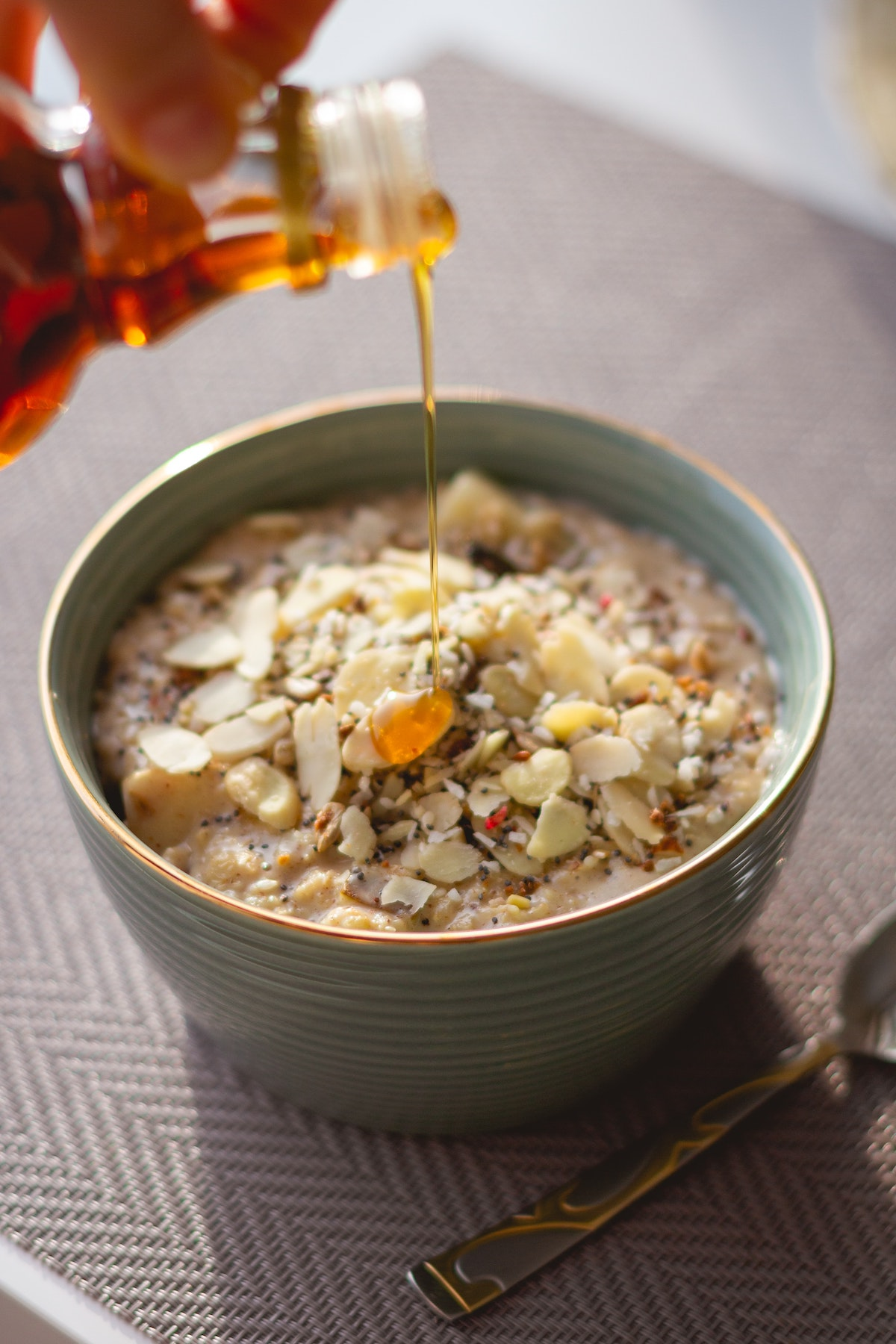 Oatmeal in a bowl with some extra nuts and grains added and maple syrup being poured over.