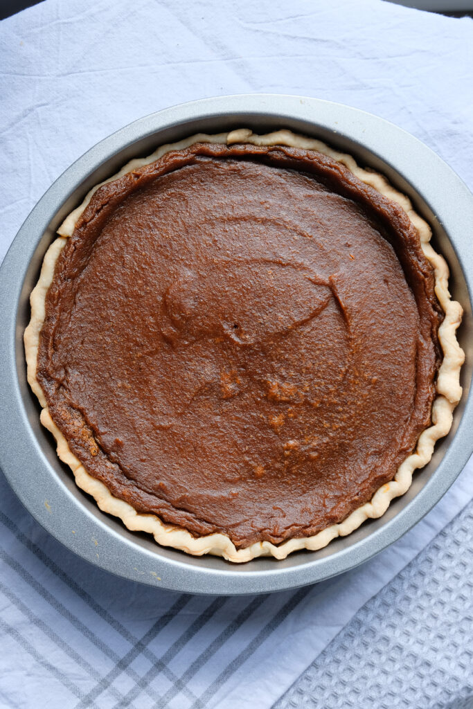 A vegan pumpkin pie cooling off in the pie plate on a table covered with kitchen towels.