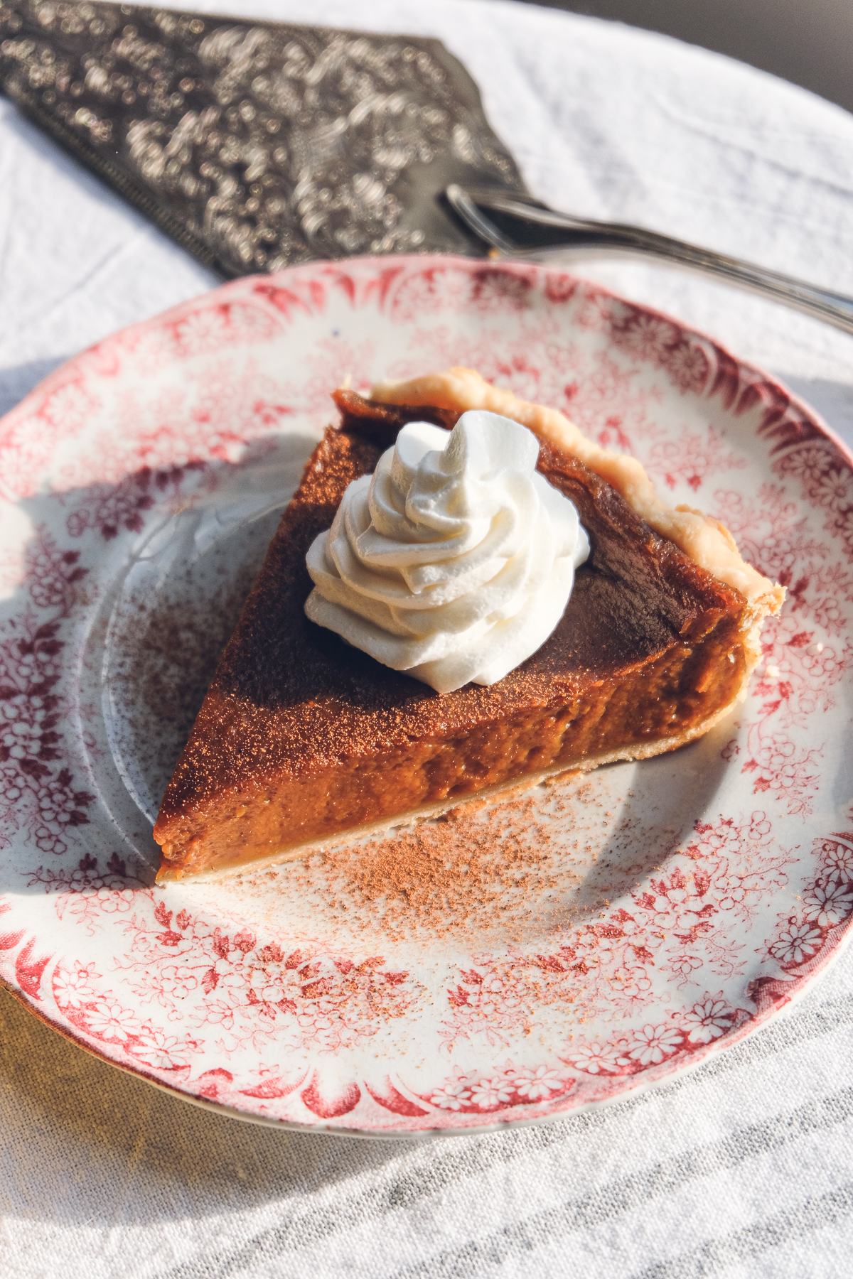 A slice of vegan pumpkin pie on a plate, topped with a spiral of whipped cream.